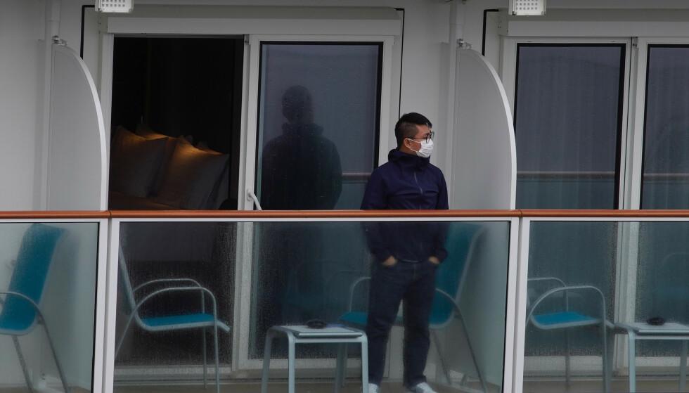 En passasjer ser ut fra cruiseskipet World Dream, som er i karantene i Hongkong. Foto: Vincent Yu / AP / NTB scanpix