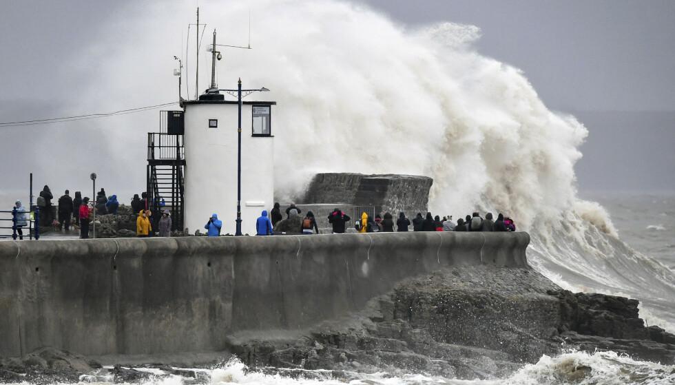 Skuelystne samlet seg lørdag på en molo i Porthcawl i Wales for å se på bølgene, til tross for advarsler fra myndighetene. Ekstremværet Dennis feide lørdag inn over De britiske øyer. Foto: AP / NTB scanpix