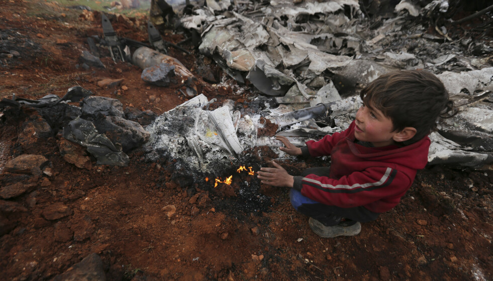 En syrisk gutt varmer seg på hendene ved vraket av et regjeringshelikopter som ble skutt ned over landsbygda vest for Aleppo by i forrige uke. Bildet ble tatt fredag. Foto: Ghaith Alsayed / AP / NTB scanpix