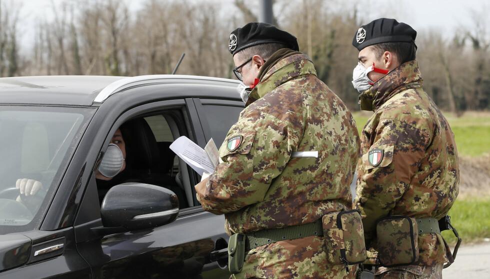 Virusutbruddet har gitt gode tider for svindlere i Italia. Her sjekker soldater biler som kjører til og fra områder i Turano Lodigiano i Nord-Italia, ett av stedene som er isolert som følge av utbruddet. Foto: Antonio Calanni / AP / NTB scanpix
