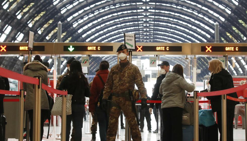 Politifolk og soldater med ansiktsmasker sjekker passasjerer på den største jernbanestasjonen i Milano mandag. Foto: Antonio Calanni / AP / NTB scanpix