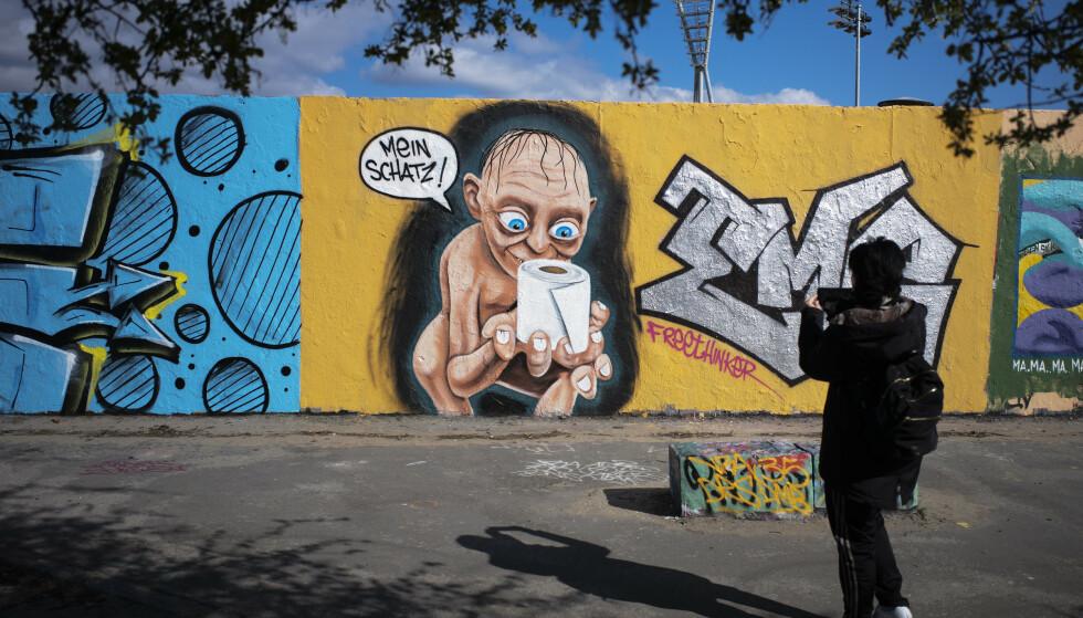 Graffiti som viser Gollum fra Ringenes Herre med en rull toalettpapir har dukket opp på muren i Mauerpark i Prenzlauer Berg i Berlin. Nå innføres et omfattende kontaktforbud i Tyskland for å hindre videre spredning av koronaviruset. Foto: Markus Schreiber / AP / NTB scanpix