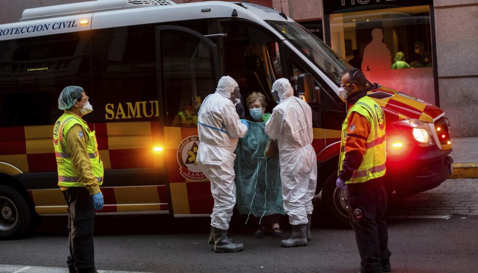 Helsepersonell henter en koronasmittet pasient i Madrid. Foto: AP / NTB scanpix