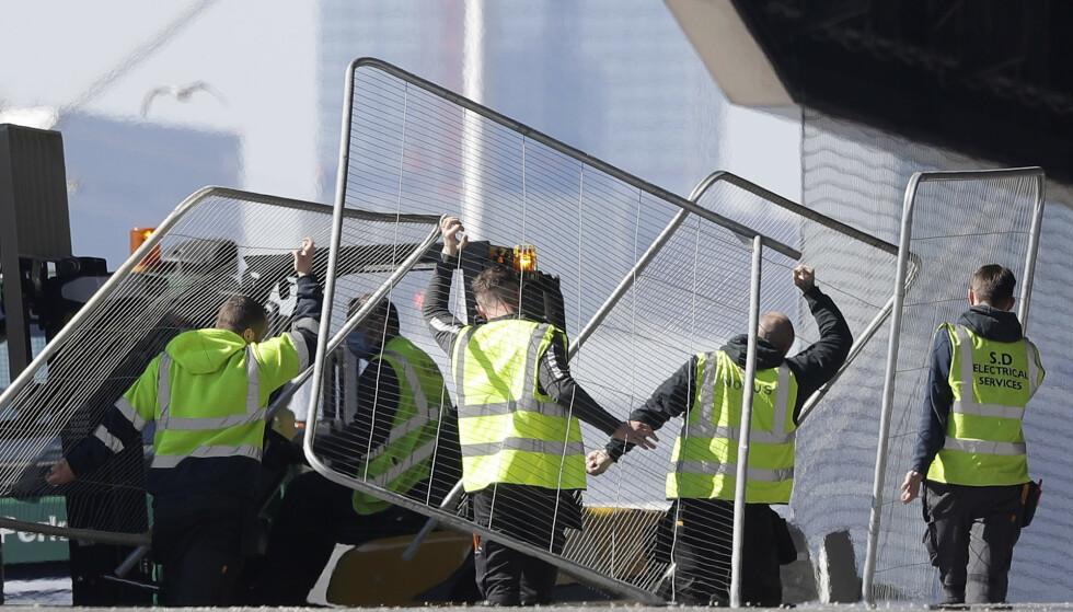 Arbeidere bærer gjerder ved Excel exhibition centre i London. Myndighetene i Storbritannia sa tirsdag at de vil omgjøre konferansesenteret til et midlertidig sykehus med 4.000 sengeplasser for å håndtere pågangen av viruspasienter. Foto: Kirsty Wigglesworth / AP / NTB scanpix