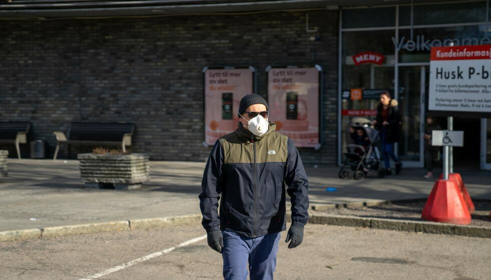 Person beskytter seg mot smitte ved bruk av munnbind og engangshansker. Illustrasjonsfoto: Thomas Brun / NTB scanpix Modellklarert