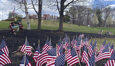 Flagg og blomsterkranser til minne om de avdøde veteranene utenfor pleiehjemmet i Holyoke. Utbruddet er trolig det verste ved en pleieinstitusjon i USA. Foto: Rodrique Ngowi / AP / NTB scanpix