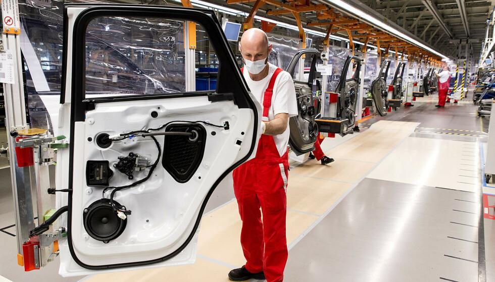 En arbeider med munnbind på en Audi-fabrikk i Gyor i Ungarn. Verdensøkonomien vil dure videre når koronakrisen er over, tror professor Kjetil Storesletten. Foto: Csaba Krizsan/MTI/AP/NTB Scanpix