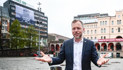 SV-leder Audun Lysbakken holdt fredag en videosendt appell på Youngstorget. Bak til venstre jobbet arbeidere med å fikse fasaden på Venstres Hus. Foto: Lise Åserud / NTB scanpix.