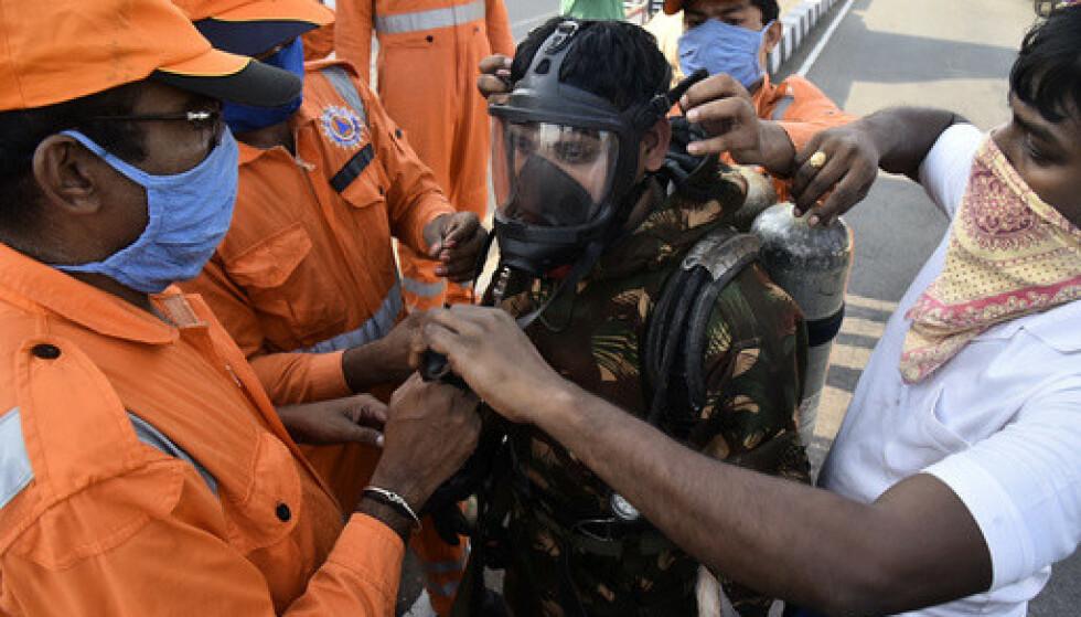 En person blir utstyrt med gassmaske før han går inn i området der gasslekkasjen skjedde i Visakhapatnam i India torsdag. Foto: AP / NTB scanpix