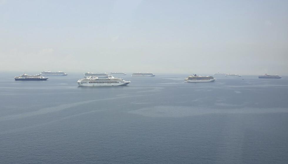 Cruiseskip som venter på å gå til kai i Manilabukta på Filippinene. Rundt 5.000 ansatte om bord på 16 skip må ta en virustest før de kan gå i land. Foto: Filippinsk kystvakt / AP / NTB scanpix