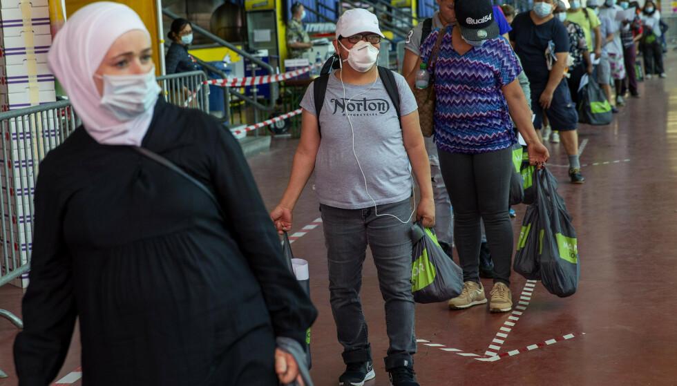 Folk står i kø for å få utdelt gratis mat i Genève i Sveits. Koronakrisen har ført til en svært vanskelig situasjon for byens vanligvis usynlige fattige. Foto: AP / NTB scanpix