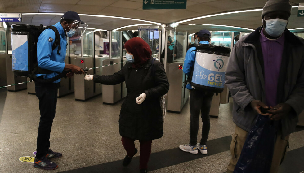 Ansatte ved metroen i Paris sprayer desinfiserende middel på hendene til pendlere. Foto: François Mori / AP / NTB scanpix
