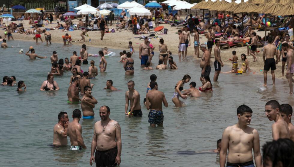 Grekere nyter vannet på en offentlig strand som ble gjenåpnet i Alimos utenfor Aten lørdag. Foto: Yorgos Karahalis / AP / NTB scanpix
