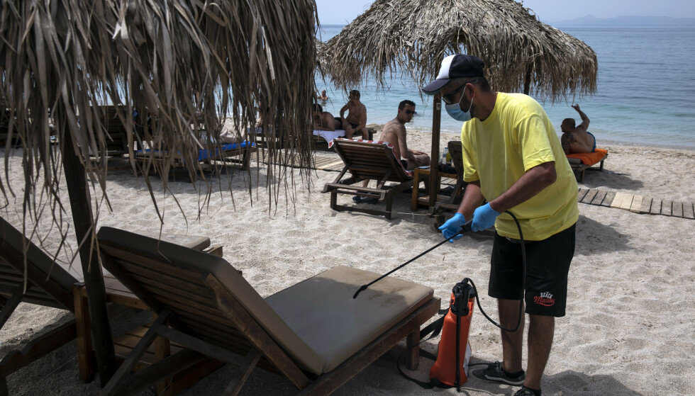 En ansatte desinfiserer en solseng for å gjøre den klar for neste badegjest på Alimos-stranda utenfor Aten lørdag. Foto: Yorgos Karahalis / AP / NTB scanpix