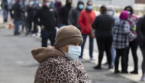 Køene utenfor kirker og veldedige organisasjoner som gir matvarehjelp, blir stadig lengre i USA. Her venter en kvinne på tur i Chelsea i Massachusetts. Foto: AP / NTB scanpix