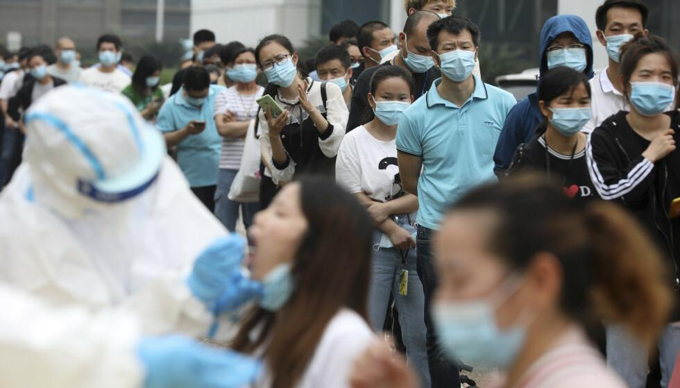Ansatte på en fabrikk i Wuhan i Hubei-provinsen blir testet for korona fredag. Foto: Chinatopix via AP / NTB scanpix