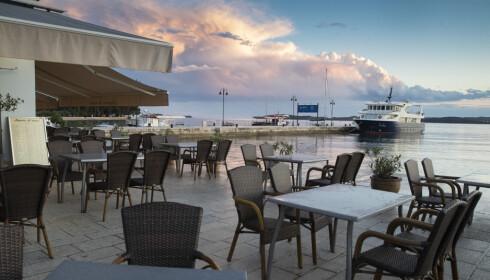 Kafeer og restauranter ligger øde i havnen i Fazana i Kroatia tirsdag denne uken. Lokalt næringsliv lider under nedstengningstiltakene. Foto: Darko Bandic / AP / NTB scanpix
