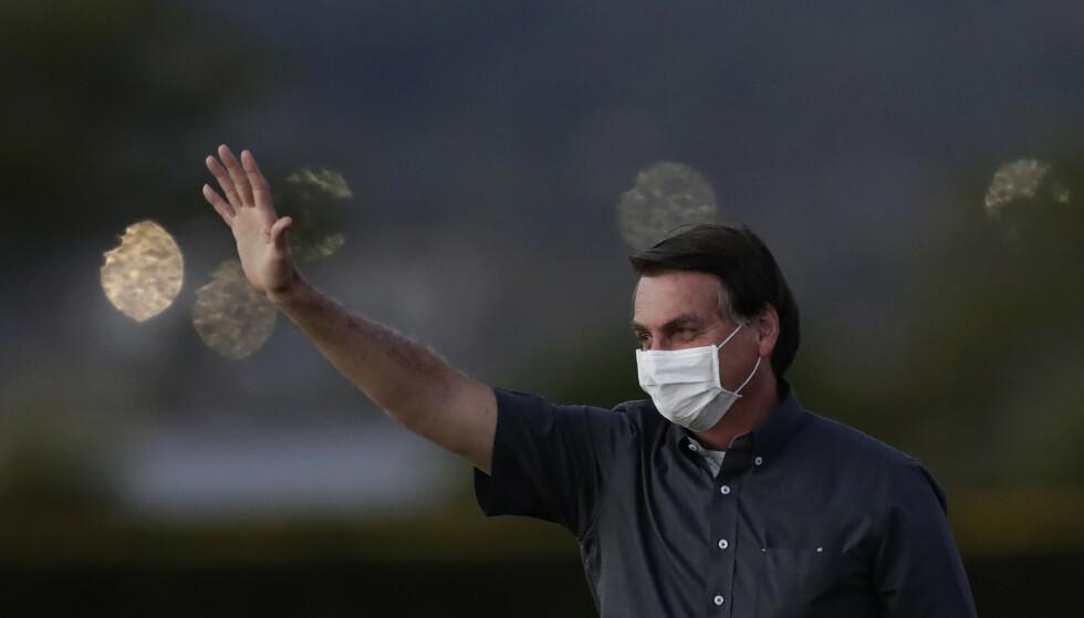 Brasils president Jair Bolsonaro er coronasmittet. På mandag vinket han til noen personer som møtte opp utenfor hans oppholdssted i Brasilia. Foto: Eraldo Peres / AP / NTB scanpix