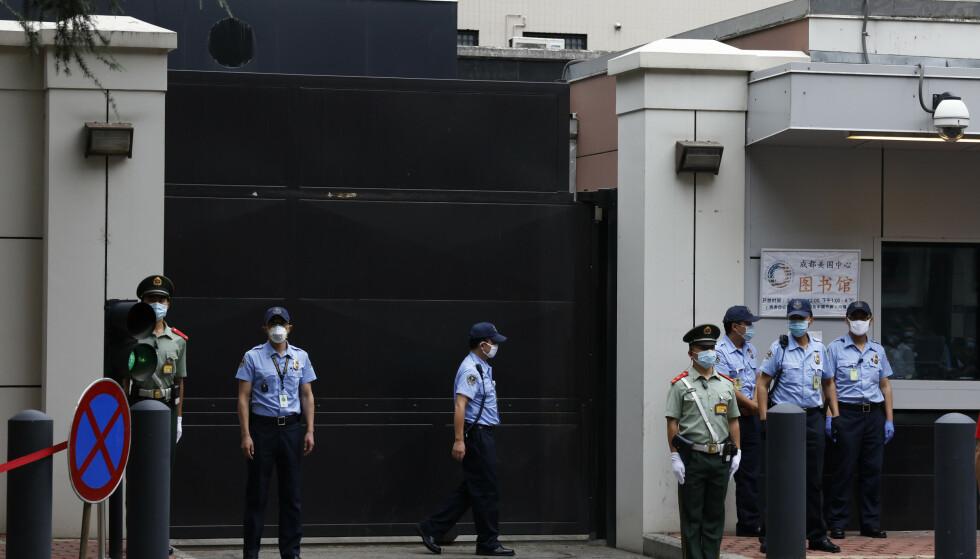 Kinesiske politifolk (i grønt) og konsulatets sikkerhetsfolk (i blått) utenfor det amerikanske konsulatet i Chengdu i Sichuan-provinsen lørdag. Konsulatet er blitt beordret stengt av kinesiske myndigheter, et ledd i en stadig mer bitter diplomatisk strid mellom de to landene. Foto: Ng Han Guan/AP/NTB Scanpix