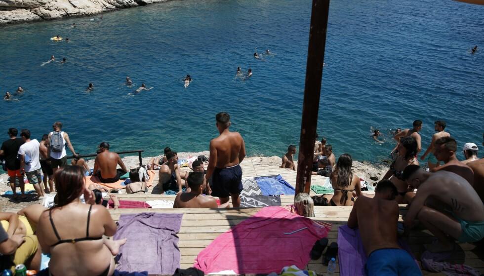 Folk koste seg torsdag i sola på Limanakia Vouliagenis, ei strand som er populær blant unge i Aten. Greske myndigheter ber folk om å ta smitteverntiltak på alvor. Foto: Thanassis Stavrakis / AP / NTB scanpix