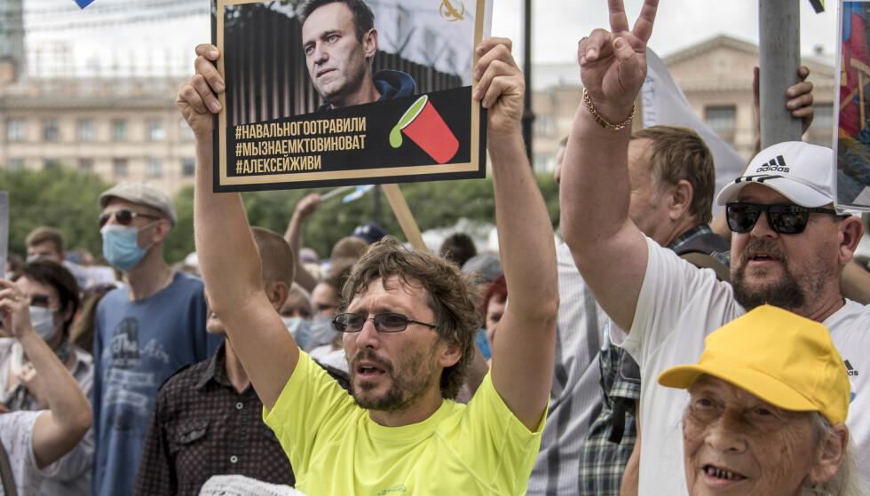 En mann holder en plakat med portrett av den russiske regimekritikeren Aleksej Navalnyj med teksten «Navalnyj ble forgiftet, og vi vet hvem som har gjorde det» under en demonstrasjon i Khabarovsk til støtte for den arresterte guvernøren i regionen Sergi Furgal. Foto: Igor Volkov / AP / NTB scanpix)