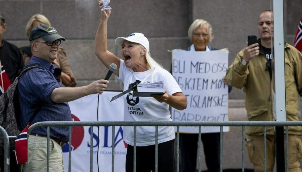 Fanny Bråten river i stykker koranen under Stopp Islamiseringen av Norges (Sian) markering på Eidsvolls plass foran Stortinget. Et massivt politioppbud sørger for å stagge motdemonstranter og Sian-tilhengere. Foto: Geir Olsen / NTB scanpix