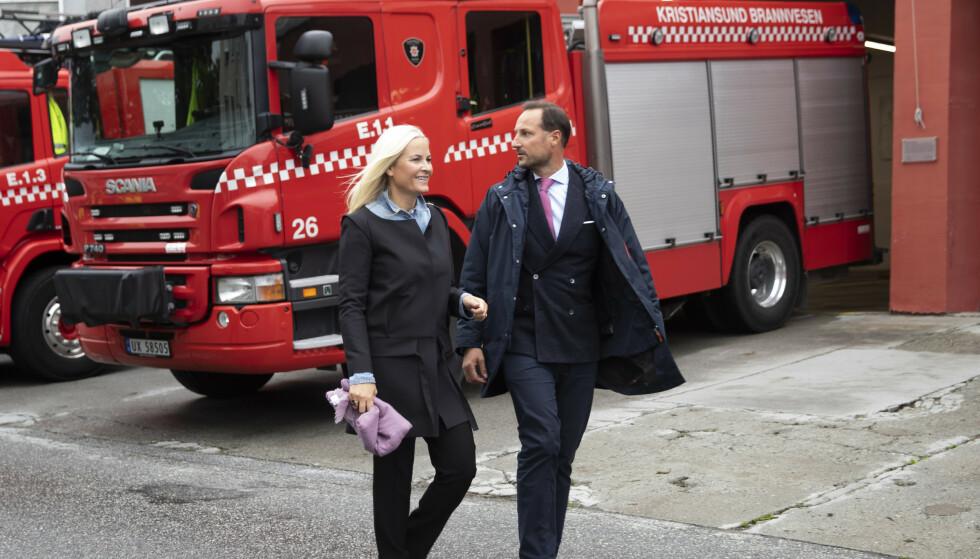Kronprins Haakon og kronprinsesse Mette-Marit ruslet tirsdag rundt i gatene i Kristiansund. Her passerer de brannstasjonen. Foto: Berit Roald / NTB.