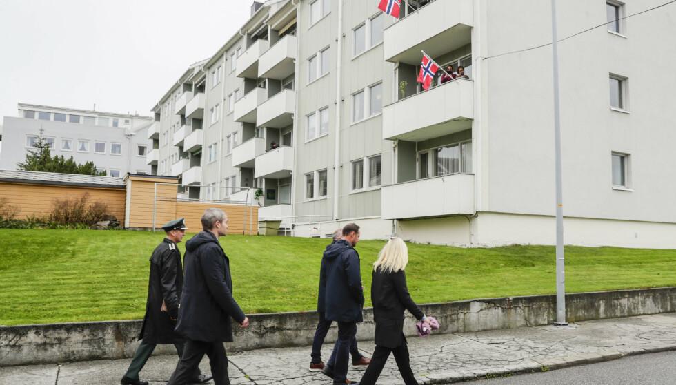 Kronprins Haakon og kronprinsesse Mette-Marit ruslet tirsdag rundt i gatene i Kristiansund. Her passerer de en boligblokk med flagg på balkongene på vei til Allanengen barneskole. Foto: Berit Roald / NTB