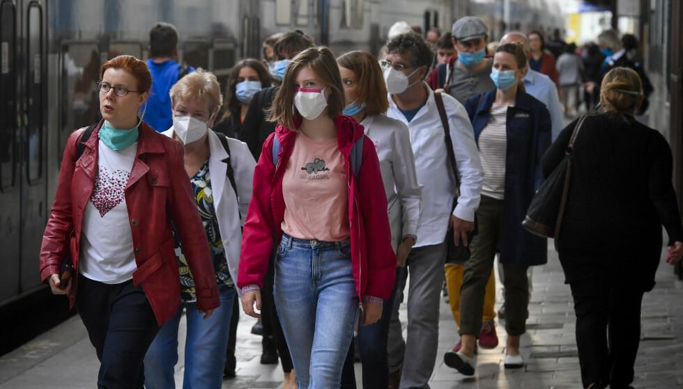 Bruk av munnbind blir stadig vanligere i europeiske byer, som her i Praha i Tsjekkia, der det nå er rekordhøy smittespredning. Foto: AP / NTB