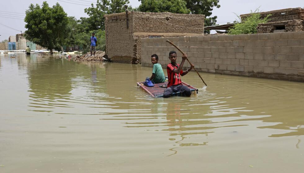 På en hjemmelagd flåte manøvrerer to unge gutter seg gjennom de oversvømte gatene i byen Salmaniya, sørvest for Sudans hovedstad Khartoum. Landet opplever nå «århundrets oversvømmelse». Foto: Marwan Ali / AP / NTB