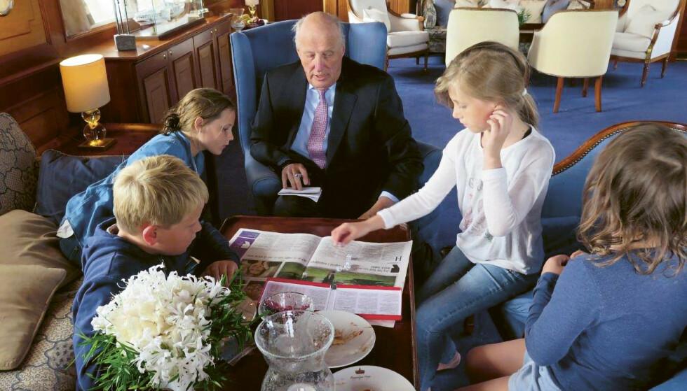 Kong Harald spiller yatzy med sine barnebarn ombord på kongeskipet. Foto: Dronning Sonja / Kagge forlag / NTB
