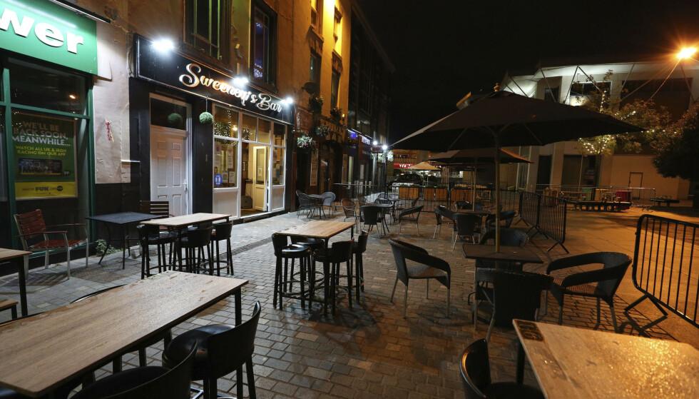 Tomme bord og stoler utenfor Sweeny's Bar i Liverpool. Nye, strenge tiltak ble iverksatt i Storbritannia denne uken. Foto: Peter Byrne/PA via AP/NTB