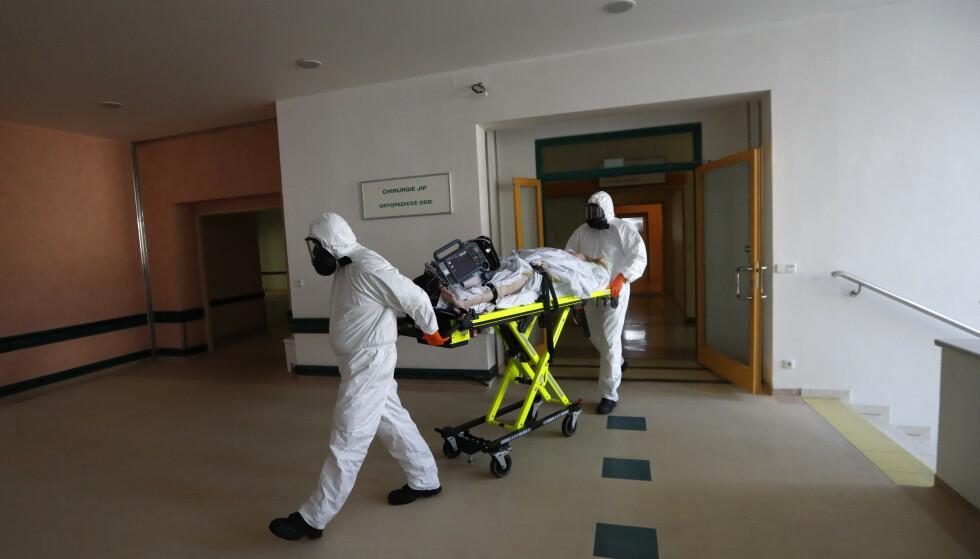 Helsearbeidere i Tsjekkia frakter en covid-19-pasient fra en intensivavdeling på et sykehus i Kyjov til et sykehus i Brno. Smitten i Tsjekkia har nådd rekordnivå to dager på rad og landets sykehus er under press med rundt 4.500 innlagte koronapasienter. Foto: Petr David Josek / AP / NTB