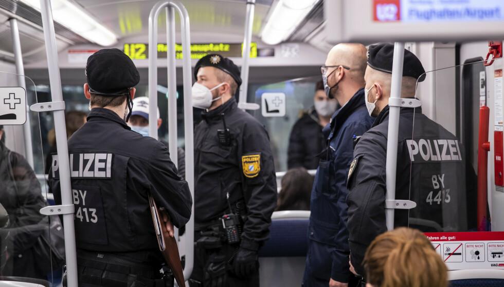 Politi foretok fredag morgen kontroll på T-banen i Nürnberg i Bayern for å sjekke om folk fulgte påbudet om bruk av munnbind. Foto: Daniel Karmann / DPA via AP / NTB