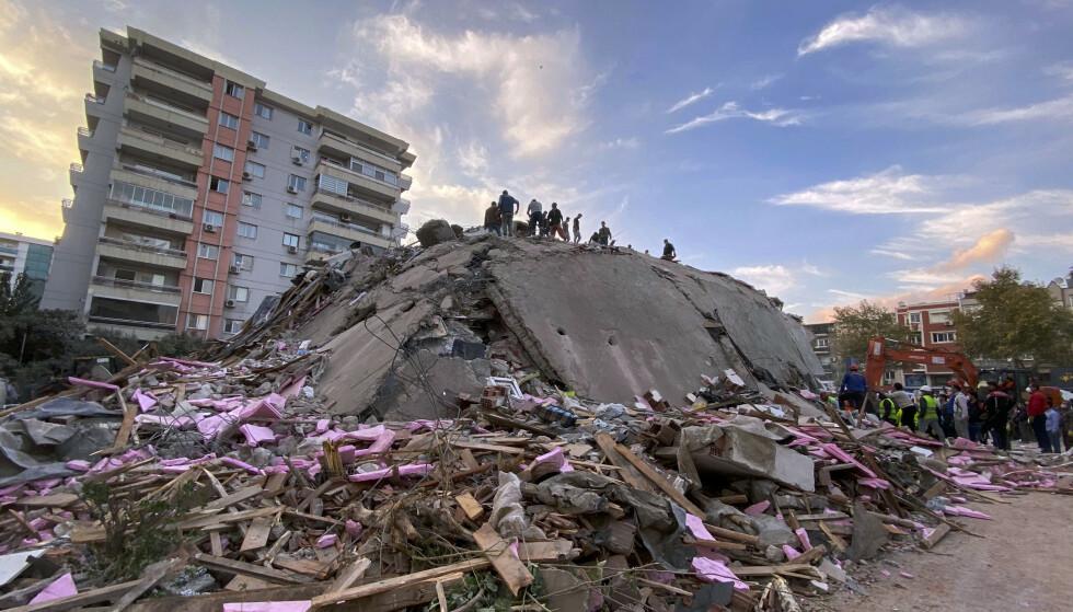 Redningsarbeidere prøver å redde folk som er fanget i ruinene av en sammenrast bygning i Izmir. Foto: AP / NTB
