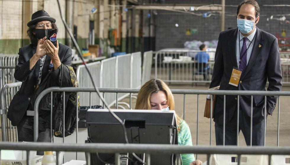 Valgobservatører ser på funksjonæren Jessica Lehman mens hun håndterer forhåndsstemmer i Pittsburgh. Foto: Andrew Rush / Pittsburgh Post-Gazette via AP / AP