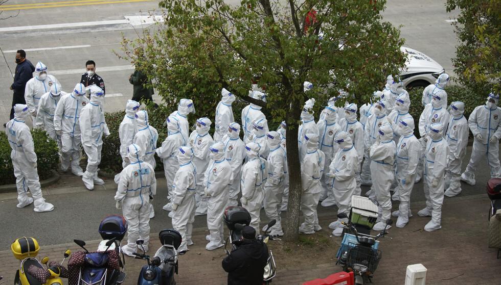 Sikkerhetsvakter i beskyttelsesdrakter er klare til å organisere massetesting av ansatte ved Pudong-flyplassen i Shanghai. Foto: AP / NTB