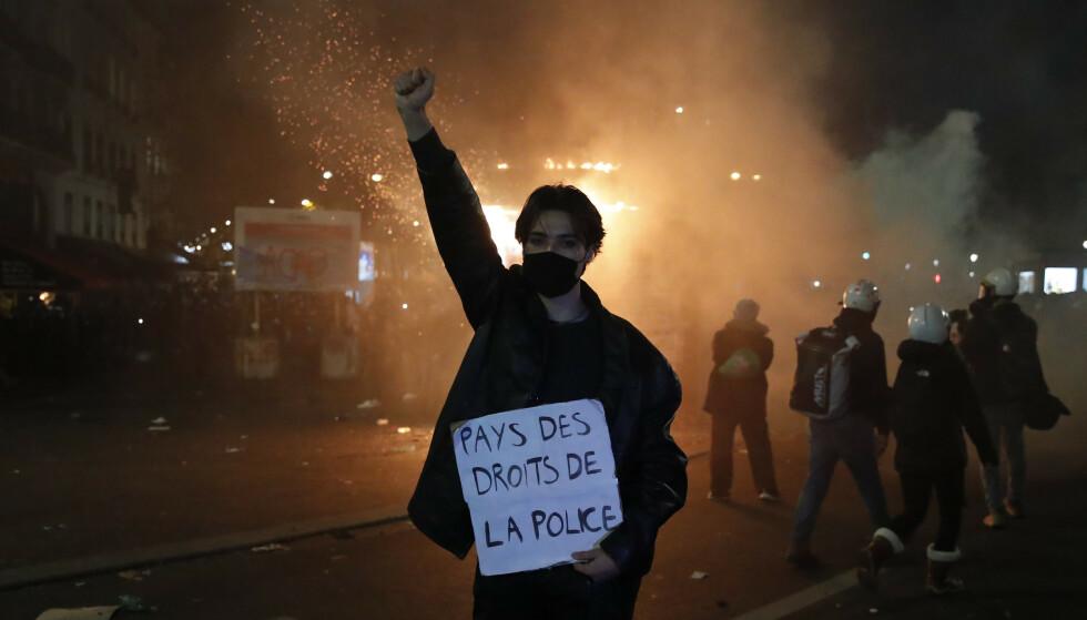 En demonstrant med en plakat med teksten «landet for politiets rettigheter» under lørdagens protest i Paris. Foto: François Mori / AP / NTB