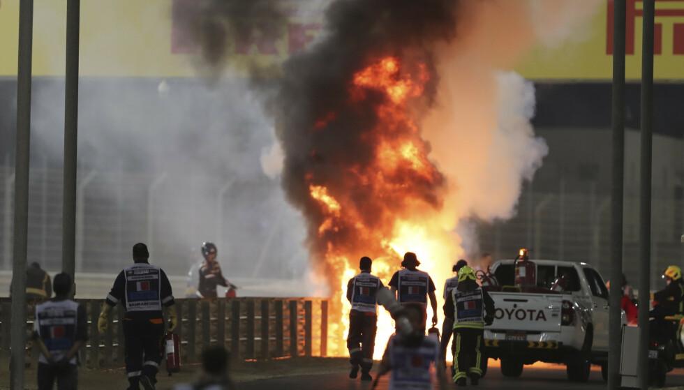 Sikkerhetsarbeidere jobber med å slukke brannen som oppsto da Romain Grosjean krasjet i Bahrain, utrolig nok kom franskmannen tilsynelatende uskadd fra hendelsen. Foto: Kamran Jebreili/AP/NTB
