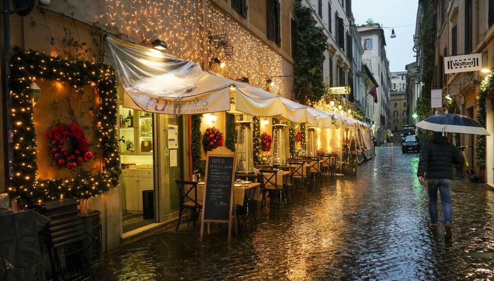 En restaurant som er pyntet til jul i en nærmest folketom gate i Roma. Foto: Andrew Medichini / AP / NTB