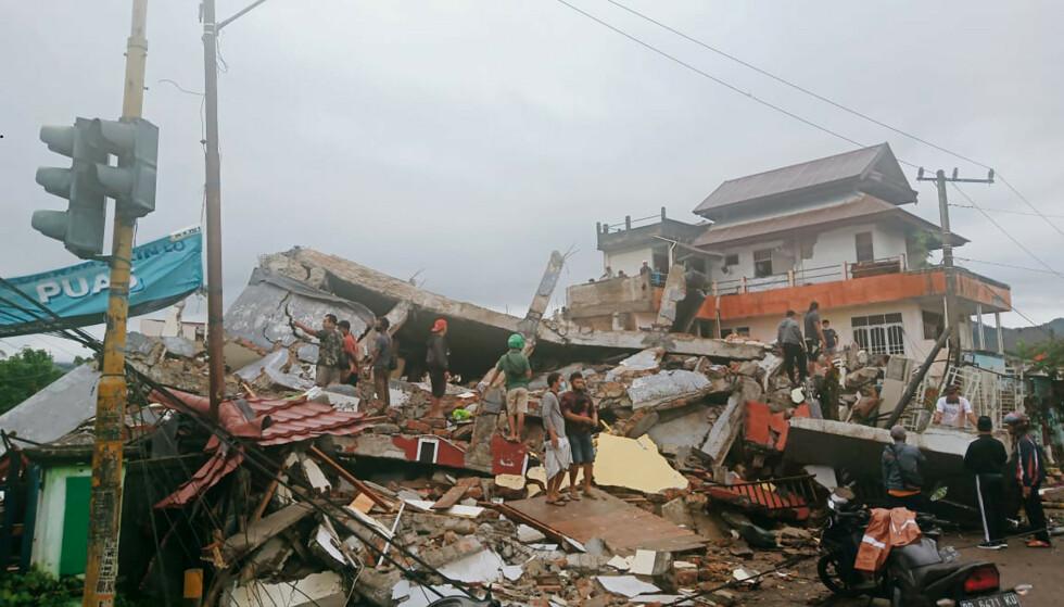 Innbyggere i Mamuju på Sulawesi i Indonesia undersøker skadene etter jordskjelvet fredag. Foto: Rudy Akdyaksyah / AP / NTB