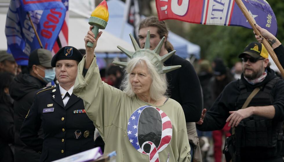 En stor Q, kjennetegnet til dem som støtter QAnon, var synlig på både flagg og klær under protestene ved Kongressen for snart to uker siden. Her pryder bokstaven kostymet til en kvinne kledd som frihetsgudinnen. Foto: Ted S. Warren / AP / NTB