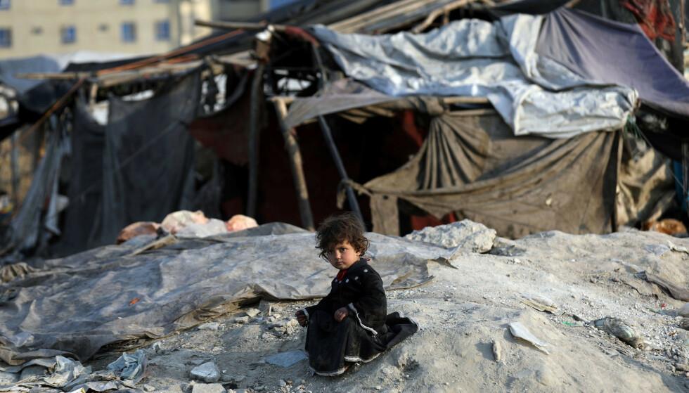 En jente utenfor sitt midlertidige hjem i en leir for internt fordrevne flyktninger i Kabul mandag. Halve befolkningen i det krigsherjede landet risikerer å gå sultne i 2021, blant dem er det 10 millioner barn, advarer Redd Barna. Foto: Rahmat Gul / AP / NTB