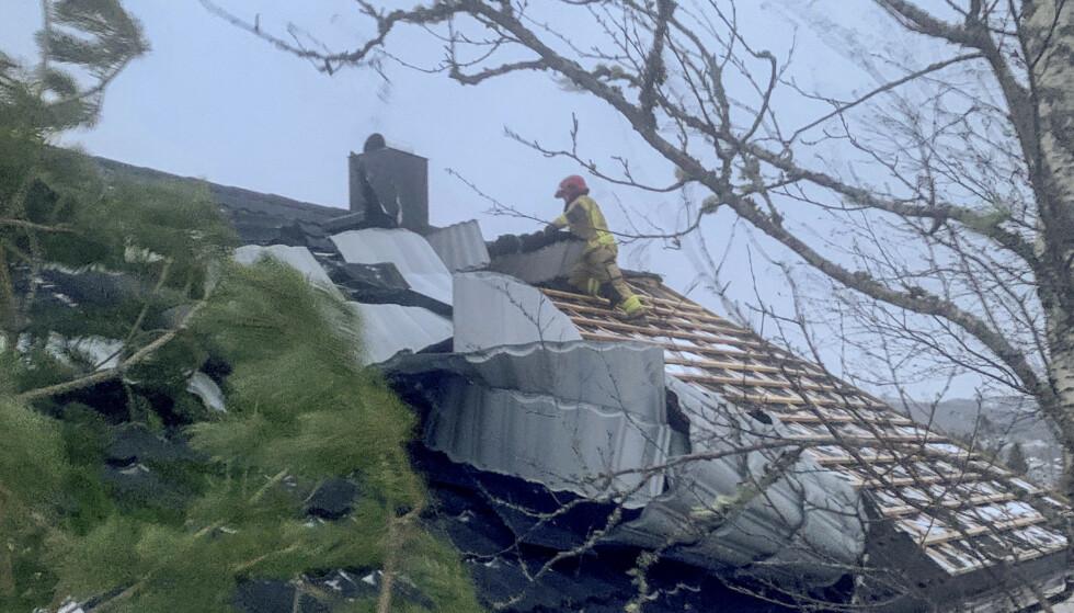 Mannskaper bra brann- og redningsetaten i Namsos sikrer taket på et hus i Ramsvikskogen der takplater har løsnet i den sterke vinden. Foto: Namsos brannvesen / NTB