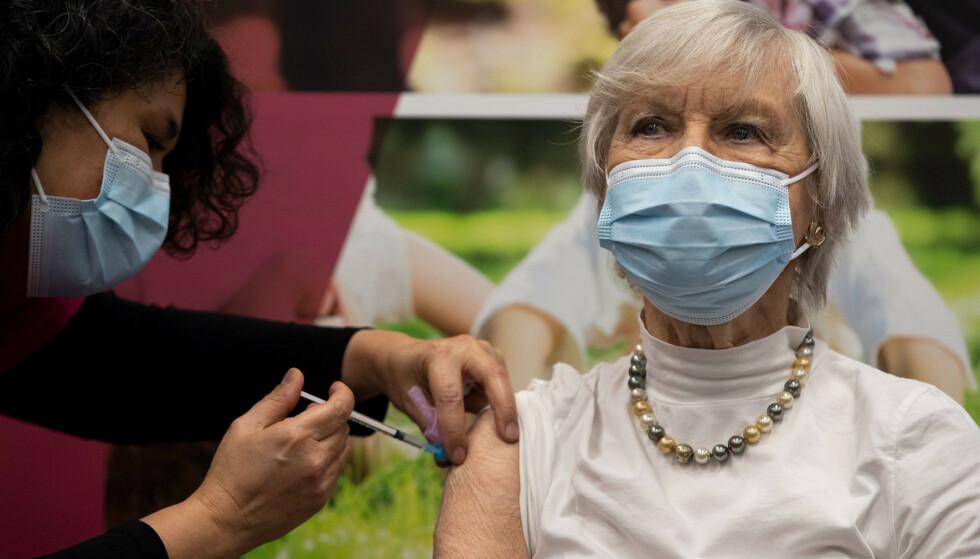 91 år gamle Ans Lock van de Veen fikk coronavaksine i Apeldoorn i Nederland tirsdag. Landet har begynt å vaksinere hjemmeboende eldre, men er samtidig også rammet av voldelige demonstrasjoner mot restriksjonene. Foto: Peter Dejong / AP / NTB
