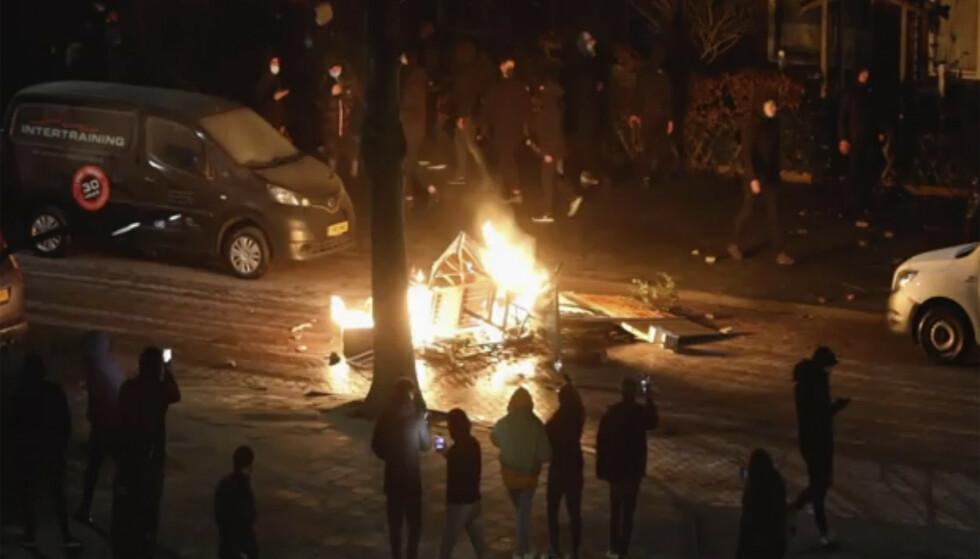 Demonstranter tente på gjenstander under opptøyer i Haarlem i Nederland mandag kveld. Foto: Mizzle Media / AP / NTB