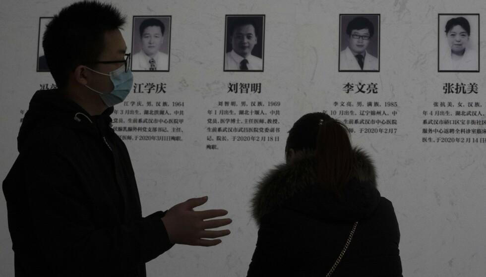 Innbyggere i Wuhan i Kina ser på en tavle som hyller helsearbeidere som har mistet livet i koronapandemien, blant dem legen Li Wenliang som først oppdaget og varslet om viruset og som selv ble smittet og døde. Foto: AP / NTB