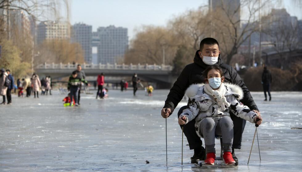 Innbyggerne i Beijing lekte på isen 30. januar. Politiet i landet har i en storaksjon pågrepet over 80 personer mistenkt for å ha produsert og solgt falske koronavaksiner. Illustrasjonsfoto: Mark Schiefelbein / AP / NTB