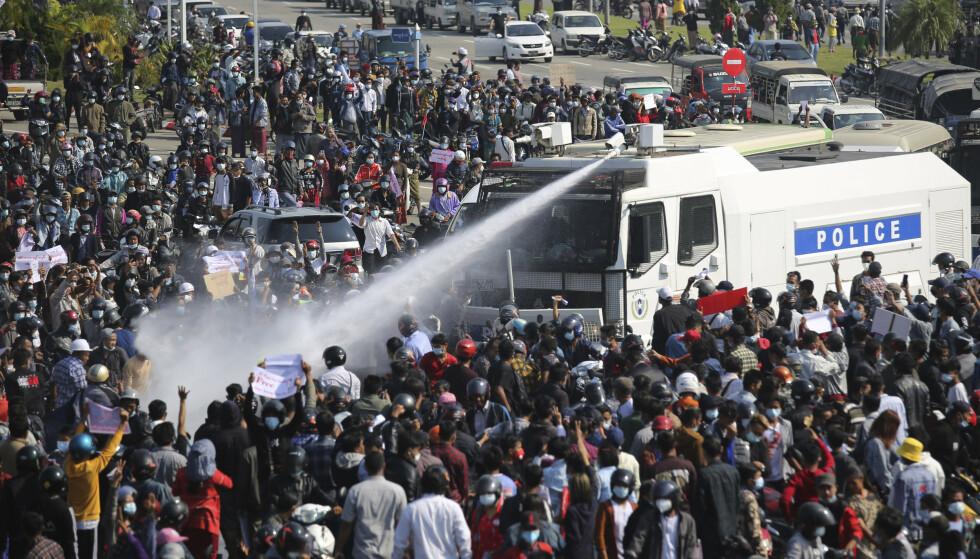 Politiet brukte vannkanoner mot demonstranter som protesterte mot militærkuppet i Myanmars hovedstad Naypyidaw mandag. Foto: AP / NTB
