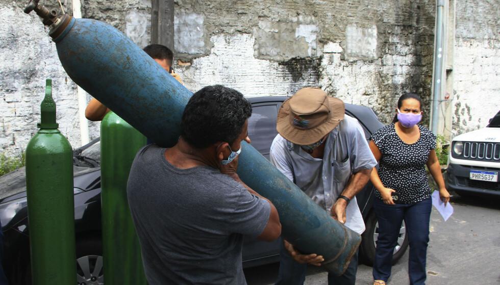 Familiemedlemmer av innlagte koronapasienter i kø i Manaus, i håp om å få fylt opp tomme oksygentanker. En virusvariant som er oppdaget i Amazonas, er ifølge Brasils helseminister tre ganger så smittsom som det opprinnelige viruset. Foto: Edmar Barros / AP / NTB
